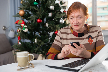 Portrait of happy senior woman using phone and laptop sitting at home against background of Christmas tree