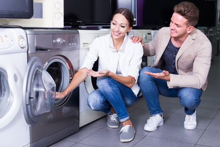 Happy family couple buying new clothes washer in supermarket Stock Photo