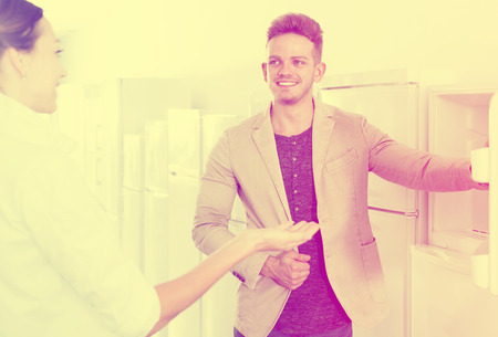 Happy young assistant in the shop sell a fridge to female customer Stock Photo