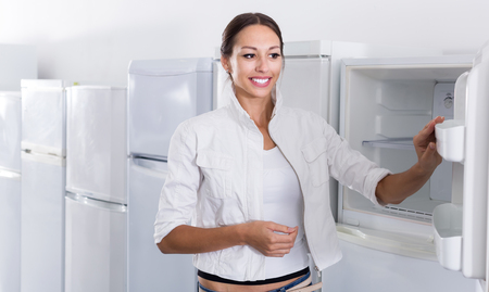 Happy woman  choosing new refrigerator in domestic appliances store