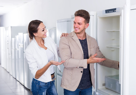 interested couple choosing new refrigerator in hypermarket electronics