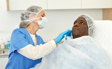 Cosmetician female examining patient face skin before aesthetic procedure in medical  office