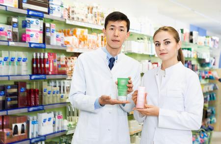 Dos especialistas serios y diligentes sostienen medicamentos y están parados en el pasillo de la farmacia.
