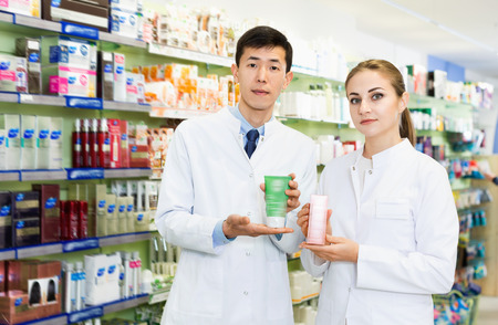 Twodiligent serious specialists are holding medicines and standing in hall of pharmacy.