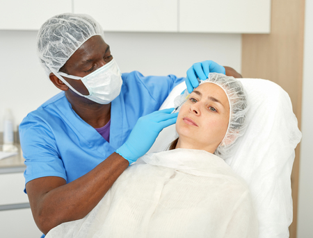Male doctor in mask is doing injection to woman patient in skin of face in estetic clinic