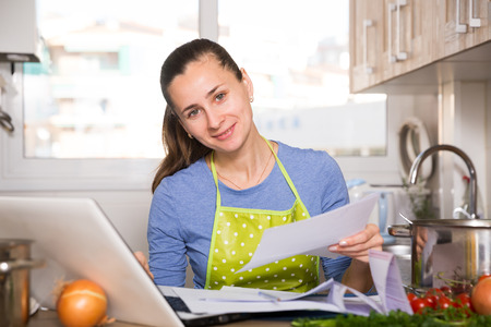 Portrait of woman filling papers and using laptop at kitchen Banque d'images