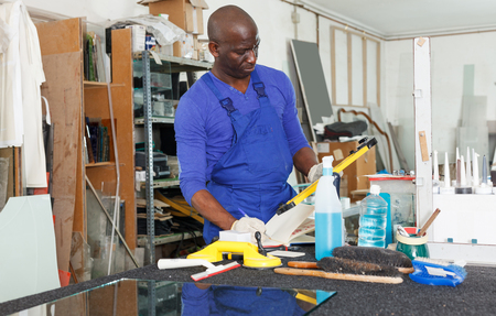 serious adult African American glass factory worker noting measurement or order data in notebook Stock Photo