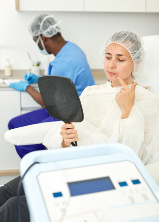 Woman sitting in armchair and looking to mirror before procedure in clinic of esthetic cosmetology Banco de Imagens