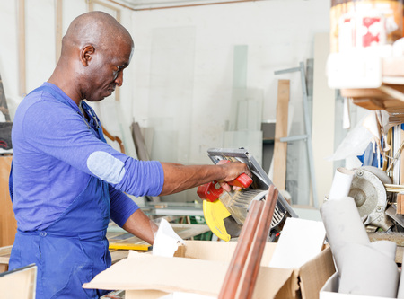 Confident African American glazier using angle grinder with thin diamond disc for glass cutting