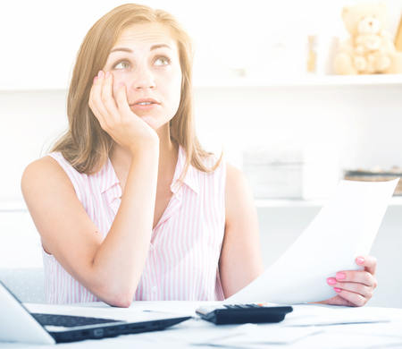 Upset girl sitting at table with laptop, looking at papers