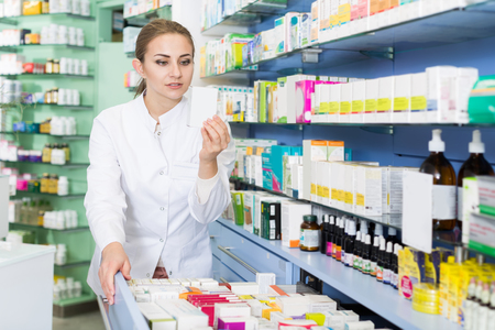 female chemist is searching medicine in drawers in apothecary.