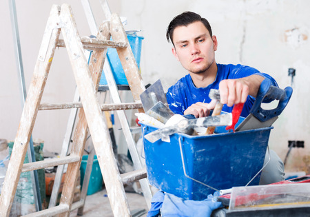 Professionality worker repairing room and looking for necessary tool in toolbox Reklamní fotografie
