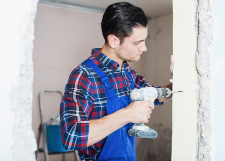 Portrait of young man worker using electric drill indoors