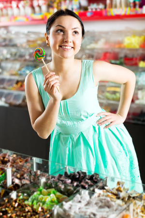 Portrait adult girl posing to photographer with lollypop at candies store Reklamní fotografie