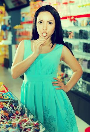 La giovane donna sexy succhia il lecca-lecca al negozio di caramelle