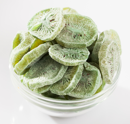 Glass bowl with sliced freeze-dried kiwi fruits on white background. Concept of healthy and diet food