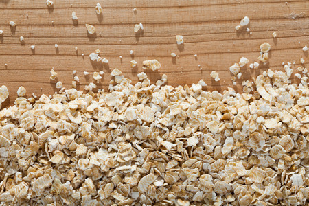 Natural background - organic oat-flakes on wooden surface