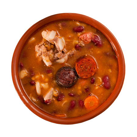 Top view of Fabada asturiana with stewed beans, pork, morcilla and chorizo served in traditional clay cazuela. Isolated over white background Stock Photo