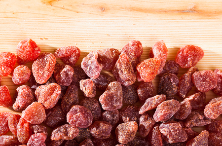 Image of dried red strawberry berries on wooden surface, nobody