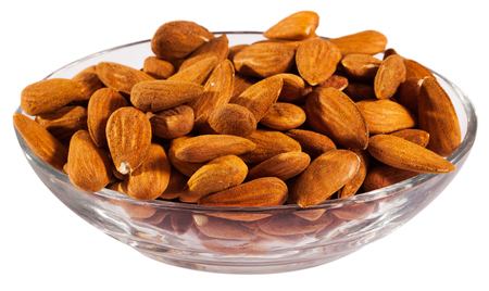 Close up of roasted salt almonds on glass bowl, nobody. Isolated over white background