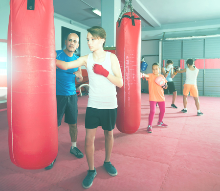 Young boxer earns blows on the punching bag under the supervision of the coach Archivio Fotografico