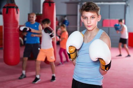 Boy boxer in gloves posing during boxing practicing at gym