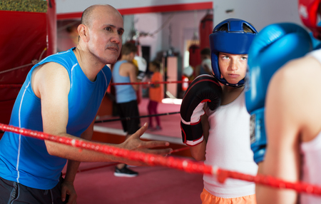 Group of children training with instructor on boxing ring at gym