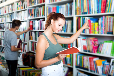 Smiling teenager girl holding open book in hands and looking at it in store 版權商用圖片
