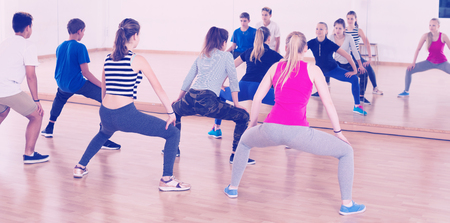 Group of teenage students with trainer stretching in dance hall