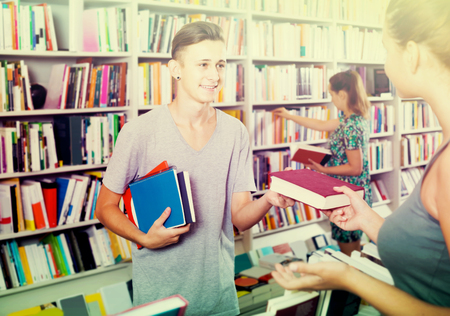 cheerful american boy teenager taking new book from seller in book store Banco de Imagens
