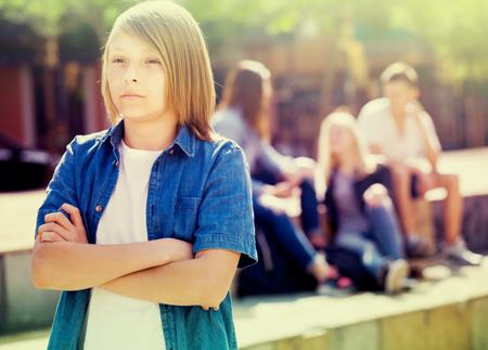 Trieste jongen tiener staat eenzaam terwijl anderen buiten praten