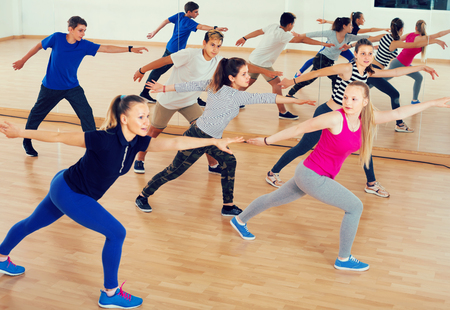 vigorous teenage boys and girls learning to dance in dance hall Reklamní fotografie