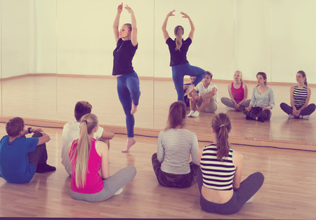 Woman dance teacher demonstrates ballet position to  students at classroom 写真素材