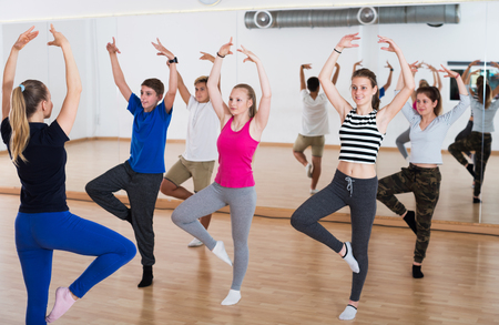 Teenage boys and girls training ballet dance in dance hall. Focus on trainer 版權商用圖片