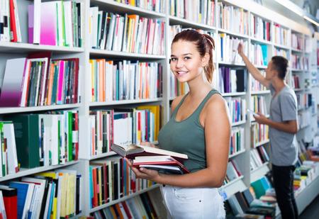 portret szczęśliwej hiszpańskiej nastoletniej dziewczyny, która patrzy na otwartą książkę stojącą wśród półek z książkami Zdjęcie Seryjne