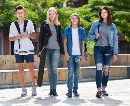 Glückliche zwei Mädchen und zwei Jungen Teenager Freunde, die zusammen im Freien spazieren gehen Standard-Bild