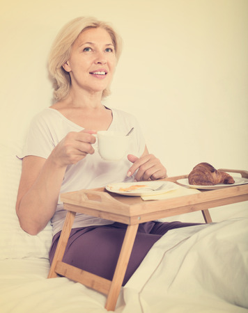 Happy mature woman enjoying breakfast in bed with croissant and coffee