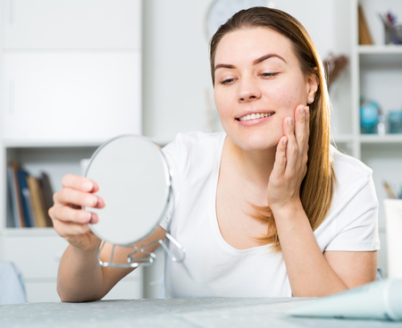 Cheerful woman is concentrared looking on her face in the mirror at the home. Фото со стока