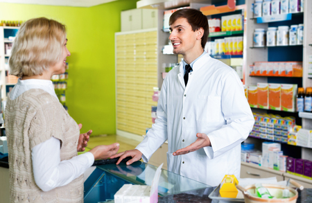 Smiling pharmacist counseling female customer in modern farmacy