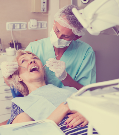 Male dentist treating mature female patient in dental office