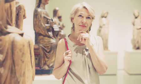 Portrait of visitor female near sculpture in the historical museum