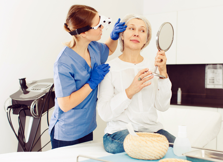 Smiling senior lady and young professional cosmetologist examining results of cosmetic face treatment
