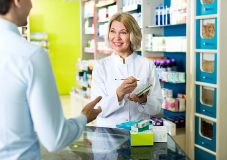 Friendly positive female pharmacist counseling customer about drugs usage in modern farmacy
