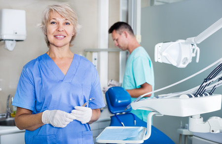Dentista de sexo femenino maduro de pie cerca del sillón dental, dando la bienvenida al paciente a una oficina Foto de archivo