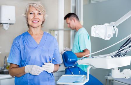 Dentista femmina matura in piedi vicino alla poltrona del dentista, accogliendo il paziente in un ufficio Archivio Fotografico