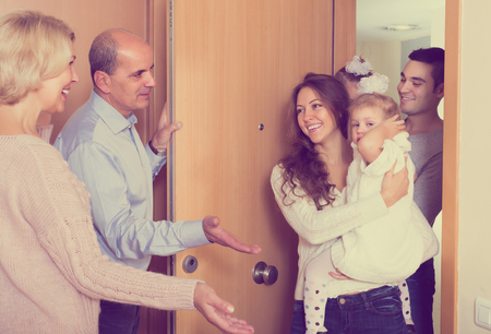 Freundliche reife Leute begrüßen liebe lächelnde Gäste mit Kindern im Innenbereich?