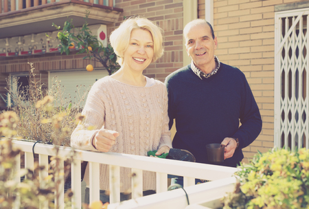 Aged smiling couple in a patio near their home. Old woman is holding gardening instruments and man is holding a cup of tea in his hand Stockfoto
