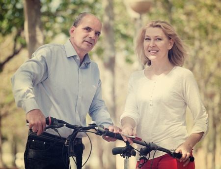 Positive senior mature couple with bicycles smiling in public garden