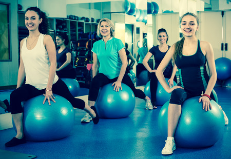 Cheerful females in fitness club having aerobic exercises with Swiss ball. Selective focus