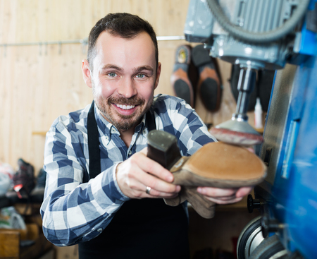 Positive adult male worker repairing shoe in specialized workshop